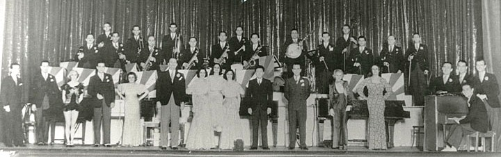 Berigan worked for Paul Whiteman from late 1932 to late 1933. Here the entire Whiteman troupe takes their bows on the stage of the Metropolitan Theater, Houston, TX, April 24,1933. Berigan is in the back row at the extreme left. A relatively svelte Paul Whiteman is in front with a black jacket and gray slacks.