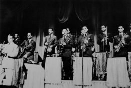 The Berigan band onstage at the Lowe's State Theater, NYC, August 24-30, 1939. L-R: Berigan; bassist Morty Stulmaker; guitarist Tommy Moore; trumpeter Joe Bauer; tenor saxophonist Don Lodice; trumpeters Johnny Napton and Jake Koven; alto saxophonist Gus Bivona; trombonist Mark Pasco; alto saxophonist Charlie DiMaggio